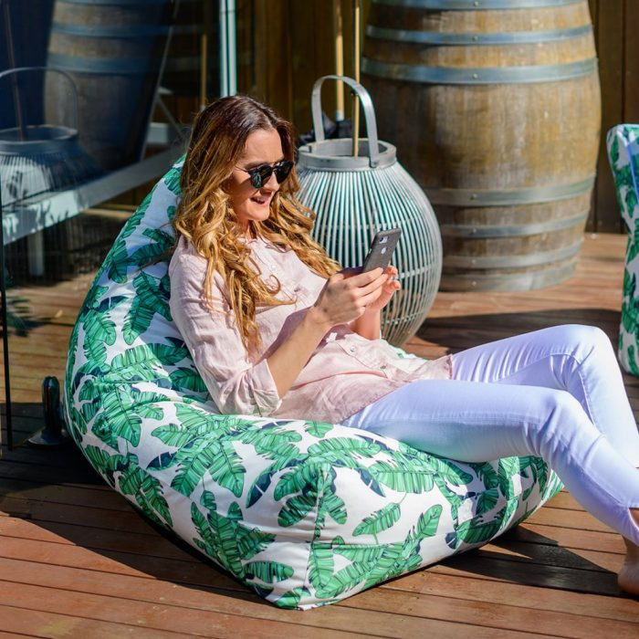 A woman looks at her phone seated on a tiki print luna bean bag on the patio