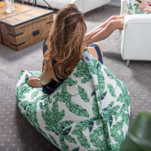 A woman sits on a leaf print luna bean bag in her home. The LiFE! branded tag can be seen