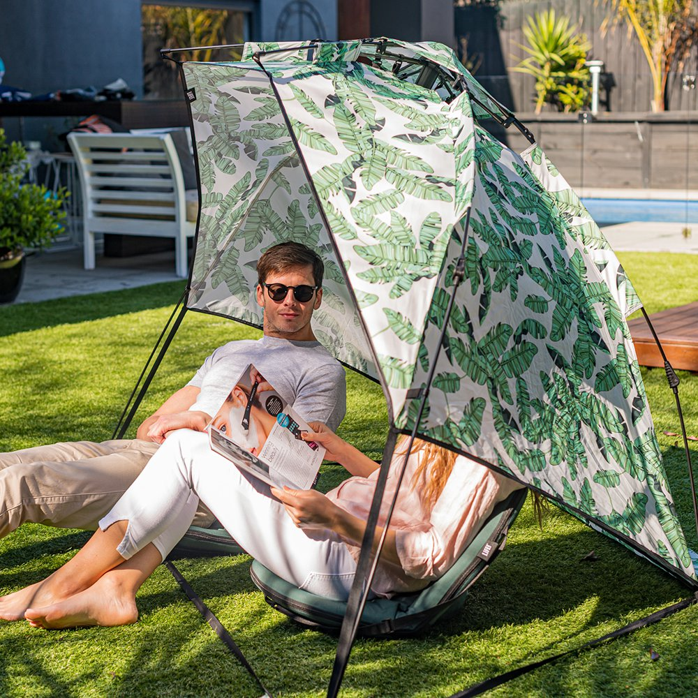 A couple sit inside a easy assemble airlie beach sun shelter
