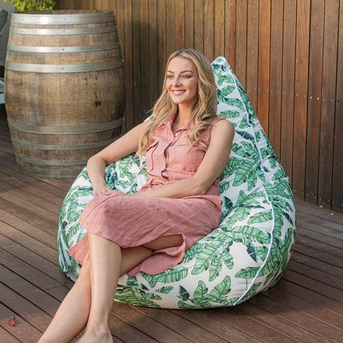 A woman sits on a super size tear drop bean bag with leaf print on her patio. The contrast white trim is visible.