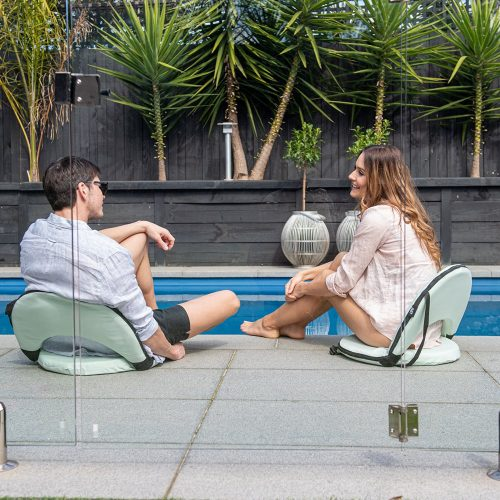 A couple sit poolside on tropical green cushion recliners