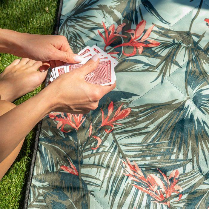 A women deals cards above a tropical print close up of a adventure mat picnic rug