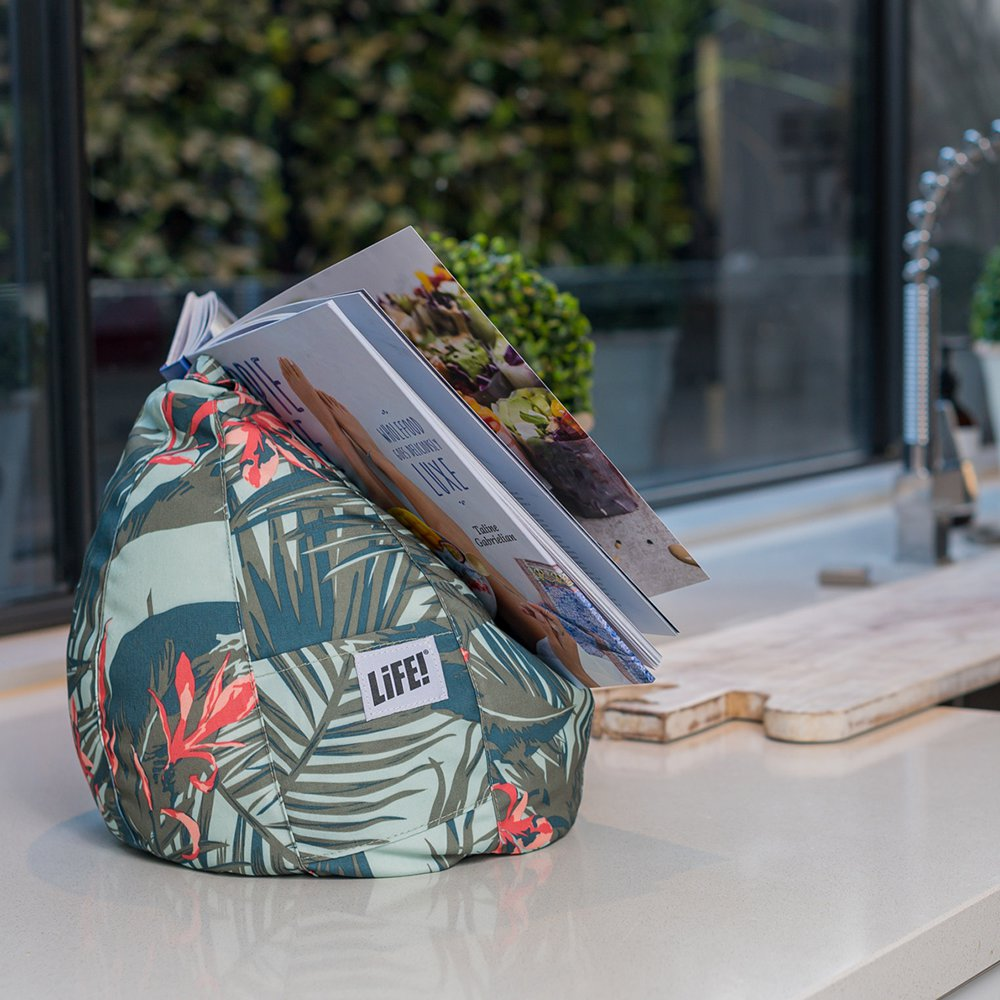 A recipe books sits on a waikiki print iCrib on the kitchen bench