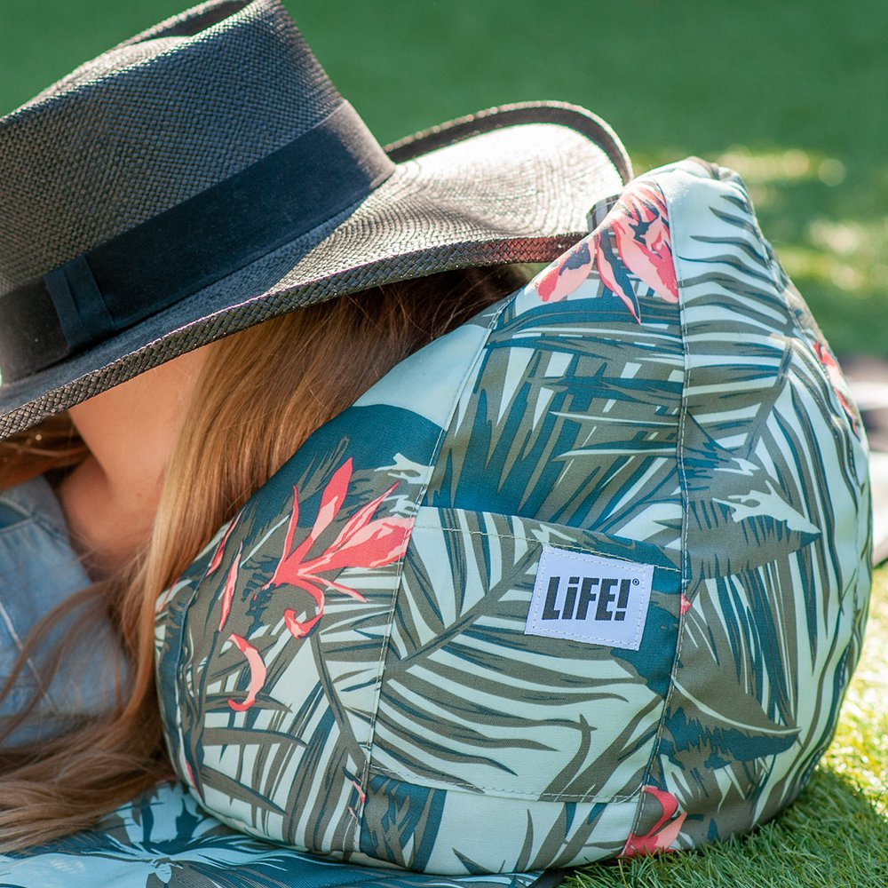 A girl snoozes on a waikiki print iCrib outdoors. The LiFE! branded tag is visible on the storage pocket