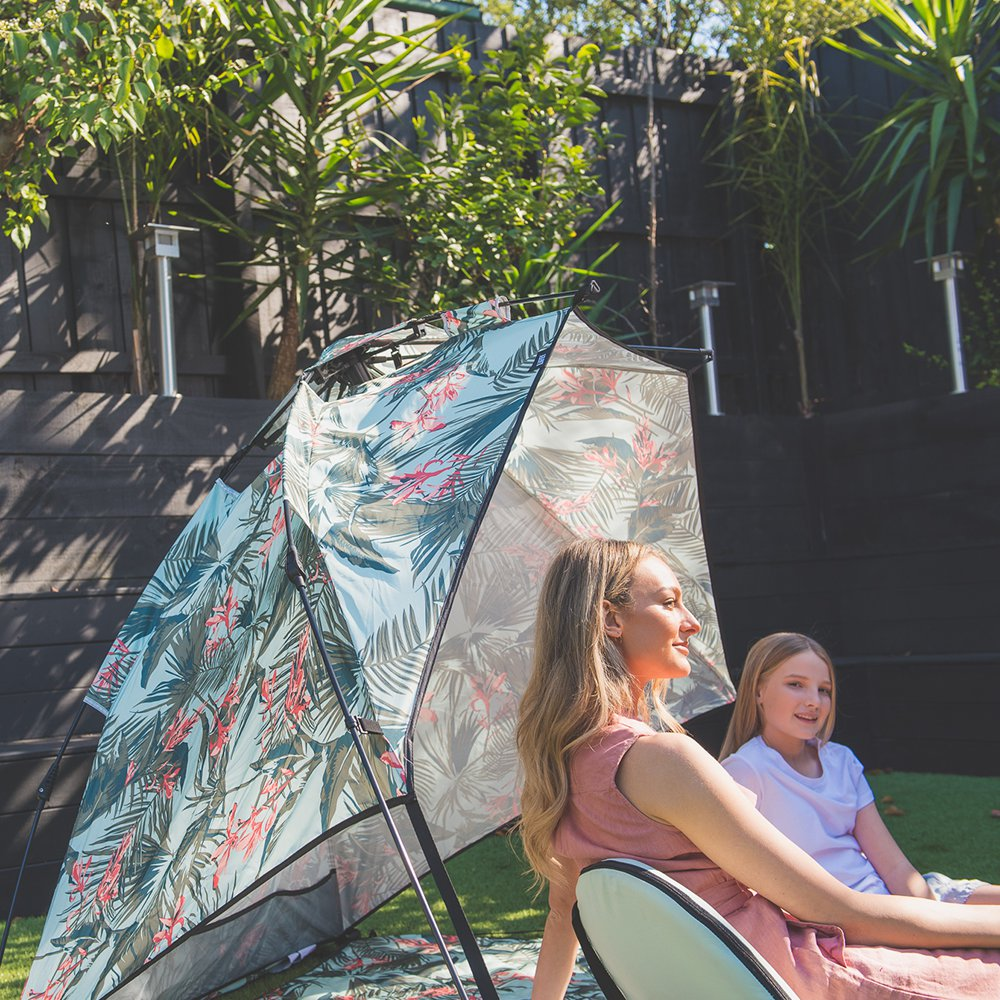 A woman and her daughter enjoy the sun under a tropical print wakiki, easy pop up, beach shelter