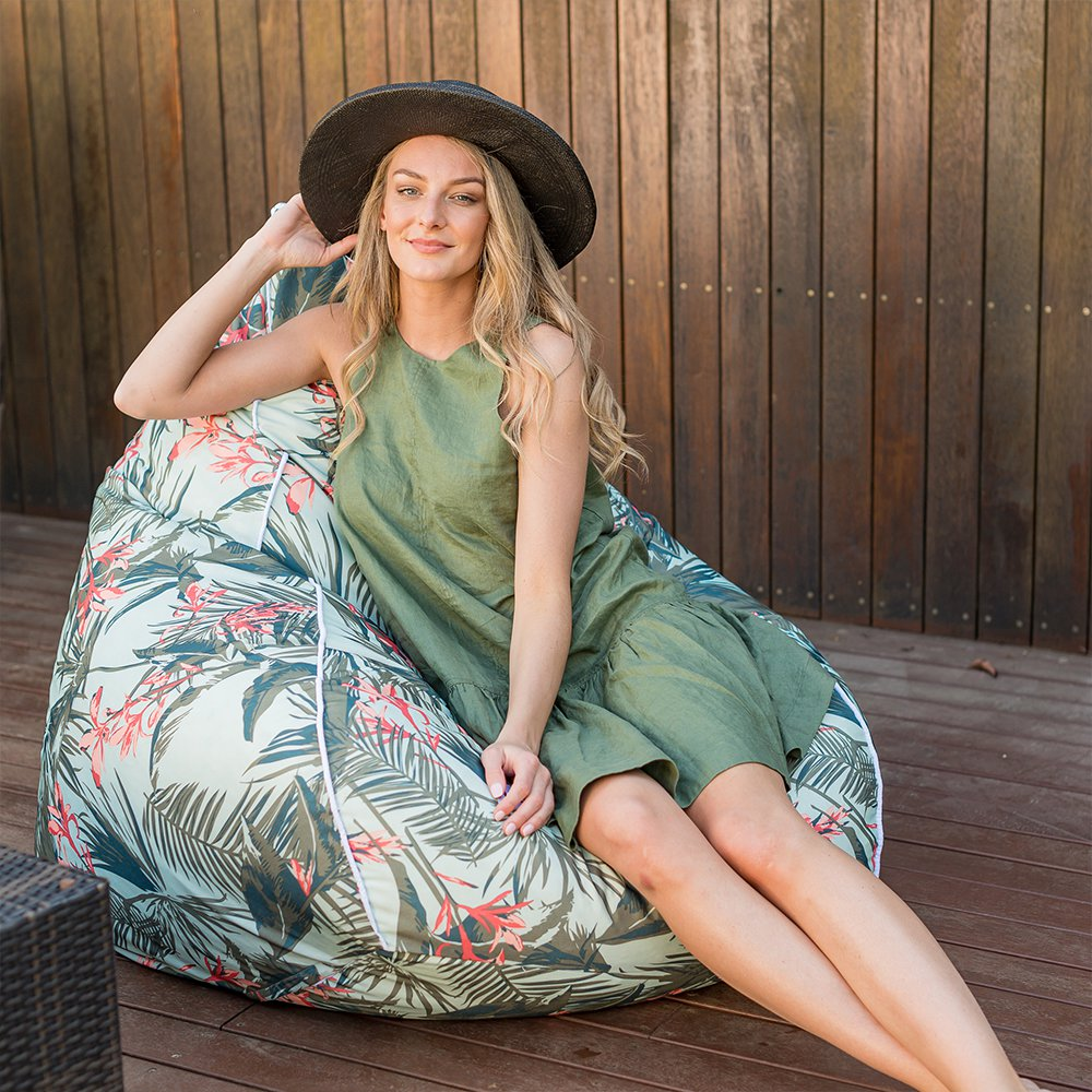 A woman sits in a super size teardrop bean bag on the patio with a tropical floral print