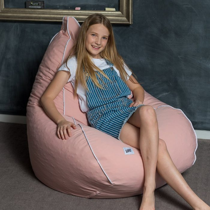 A teen sits on a soft pink coral colored teardrop shaped bean bag with contrast white trim