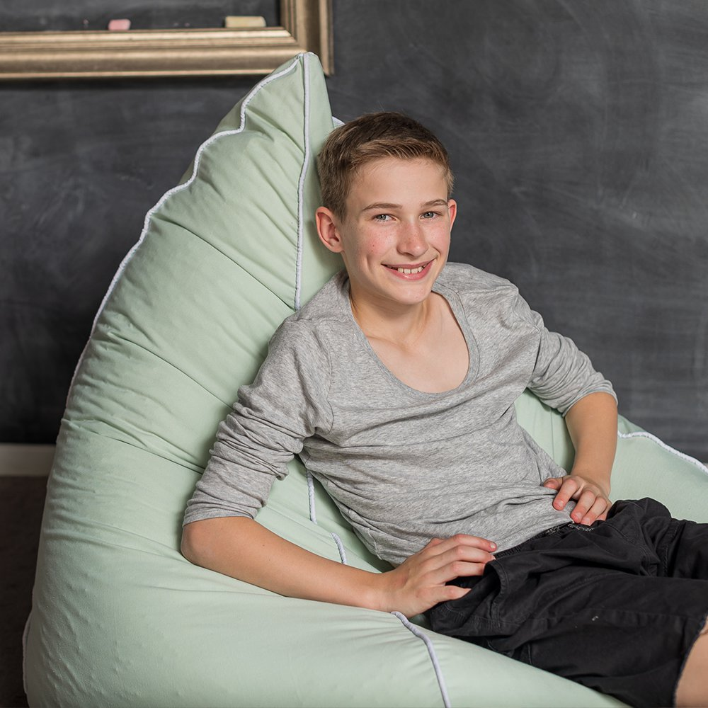A teen sits in a tropical green tear drop shaped bean bag