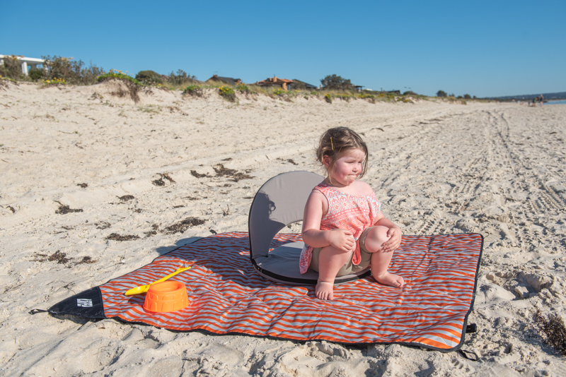 A toddler sits on a grey cushion recliner at the beach. The cushion recliner is on an oranged striped picnic rug