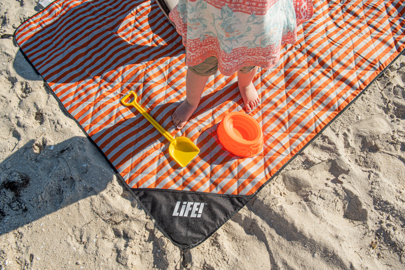 A childs feet are visible next to a bucket and spade on an orange striped adventure picnic mat