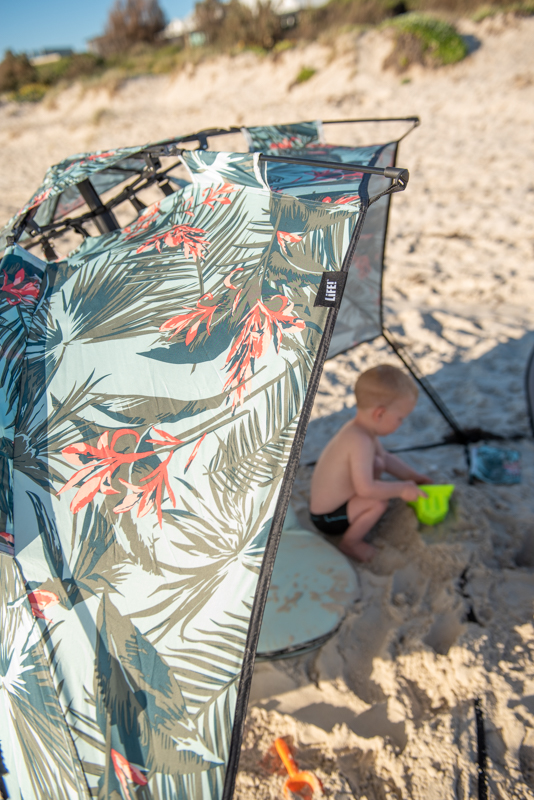 Close up of LiFE! tag on a waikiki print airlie sun shelter at the beach.