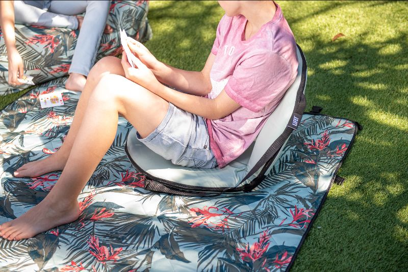 A teen sits on a tropical green cushion recliner that sits atop a waikiki floral print adventure mat