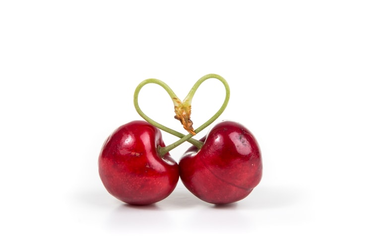 A pair of cherries make a heart with their stalk
