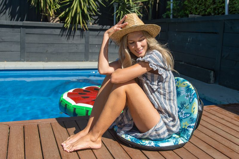 Women sits on a floral leaf print cushion recliner deckside by the pool