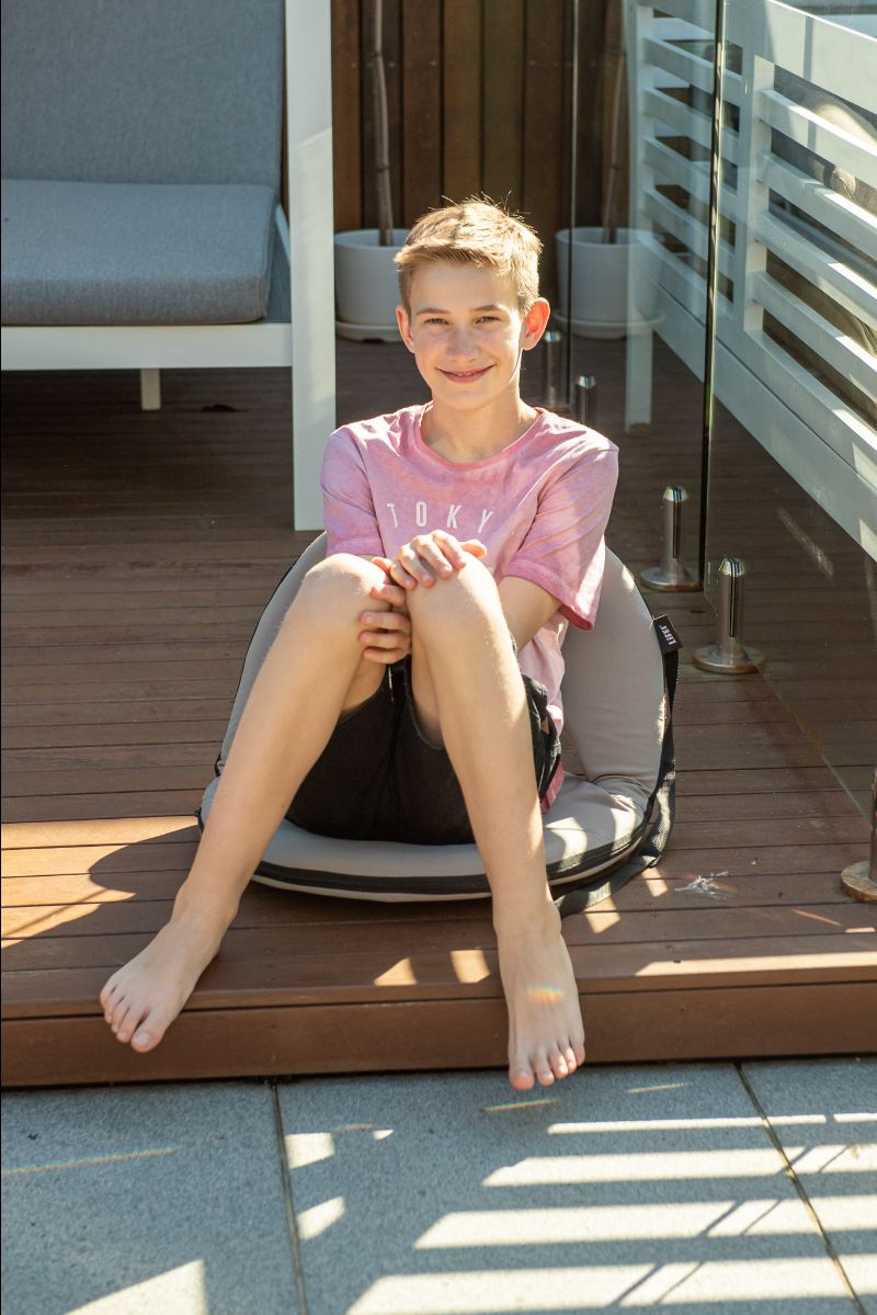 Teen sits on a grey ozark cushion recliner on some decking