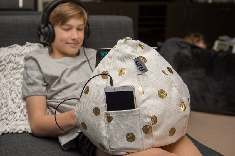 A teen listens to music and reads a book resting on a gold and white iCrib