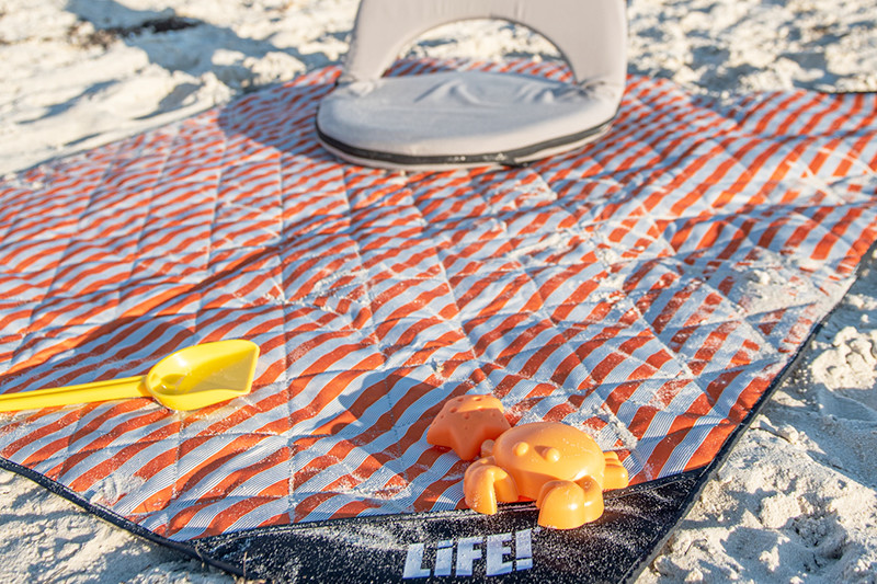 Close up of a bucket and spade atop a sandy retro stripe adventure mat at the beach