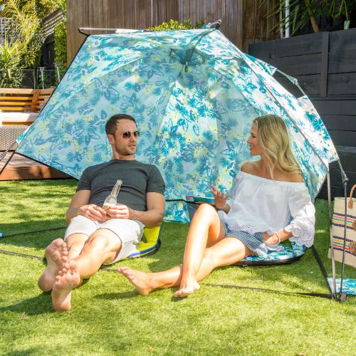 A couple sits talking and drinking in the shade of a floral leaf print sun shelter