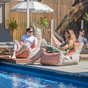 Couple recline on retro stripe coastal lounger bean bags beside a pool