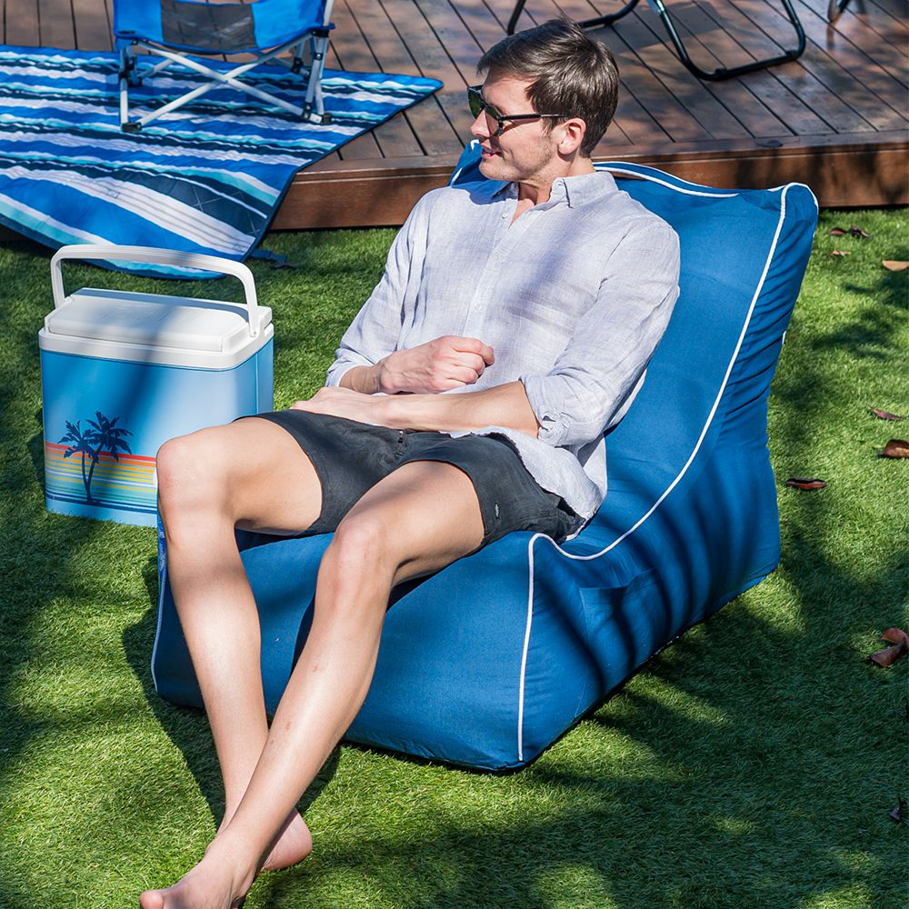 man sit in a blue steel coastal lounger bean bag in a backyard next to a cooler and deck