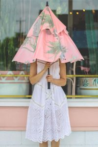 a women hides behind a kakteen rain umbrella in a white dress in front of a pink and white shop window