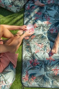 Close up of a women dealing cards above a waikiki adventure mat picnic blanket