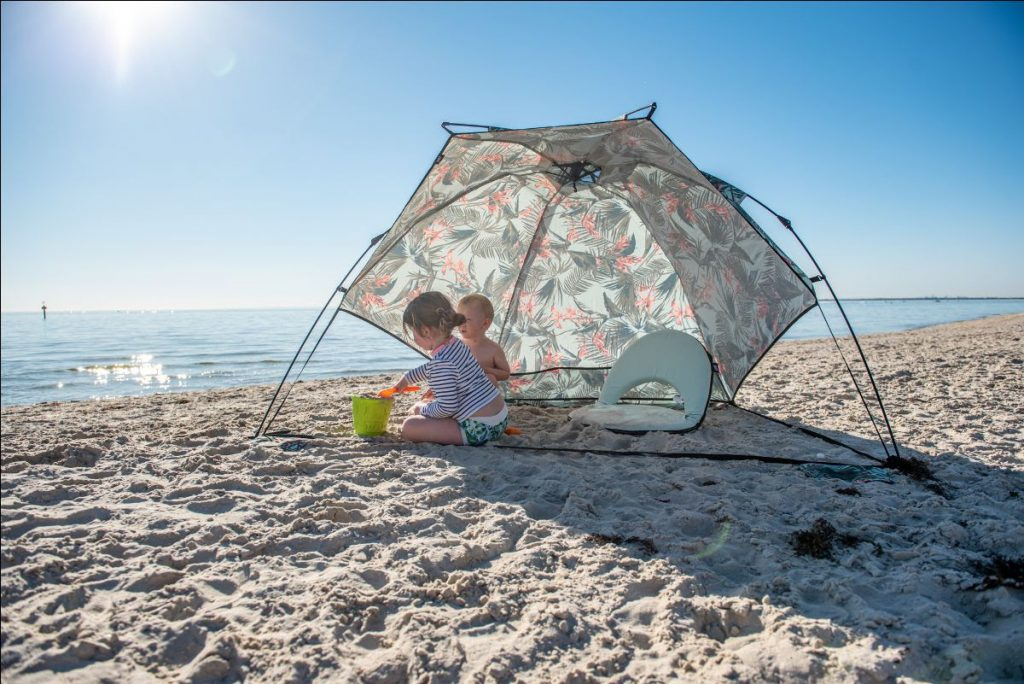 two children play on the beach shaded by an airlie sun shelter