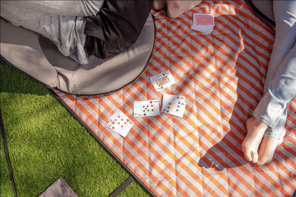 cards are scatterd on an orange retro striped picnic rug