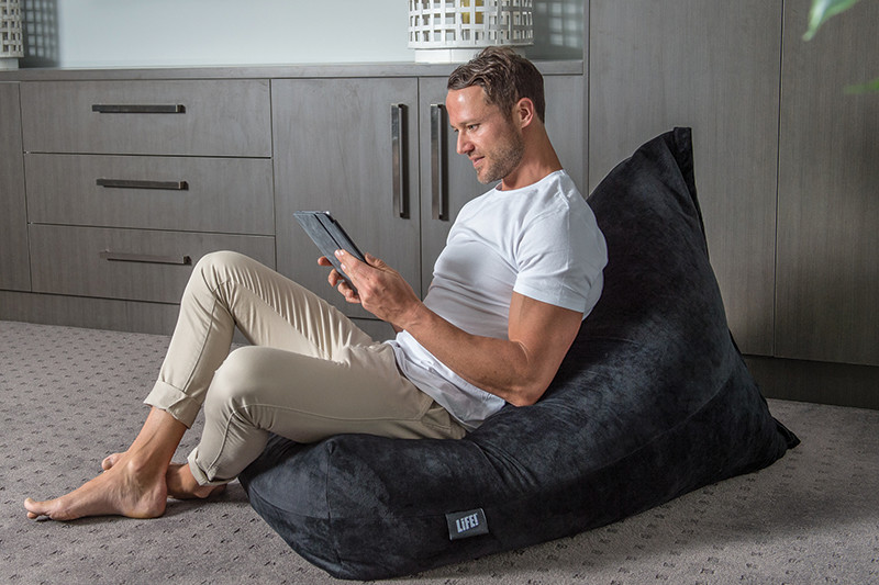 mat sits comfortably in a grey velvet luna bean bag watching a tablet or ipad