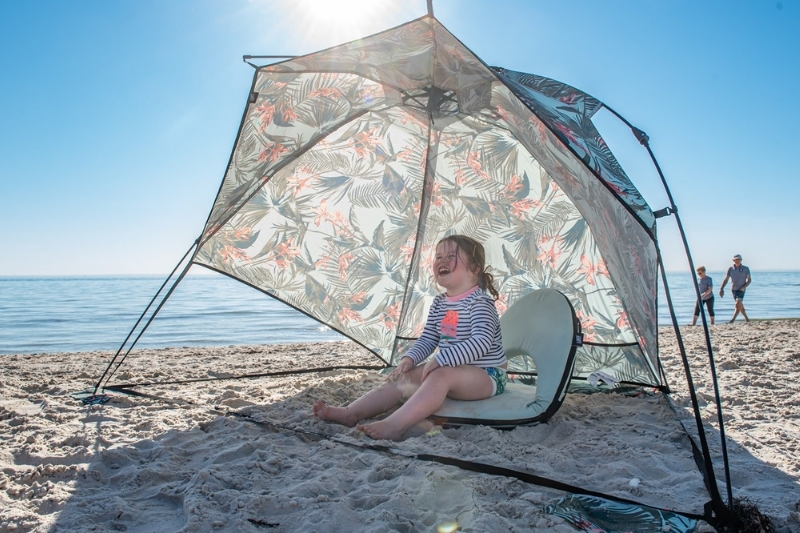 small child sits on a cushion recliner under an waikiki airlie sun shelter on the beach on a sunny day