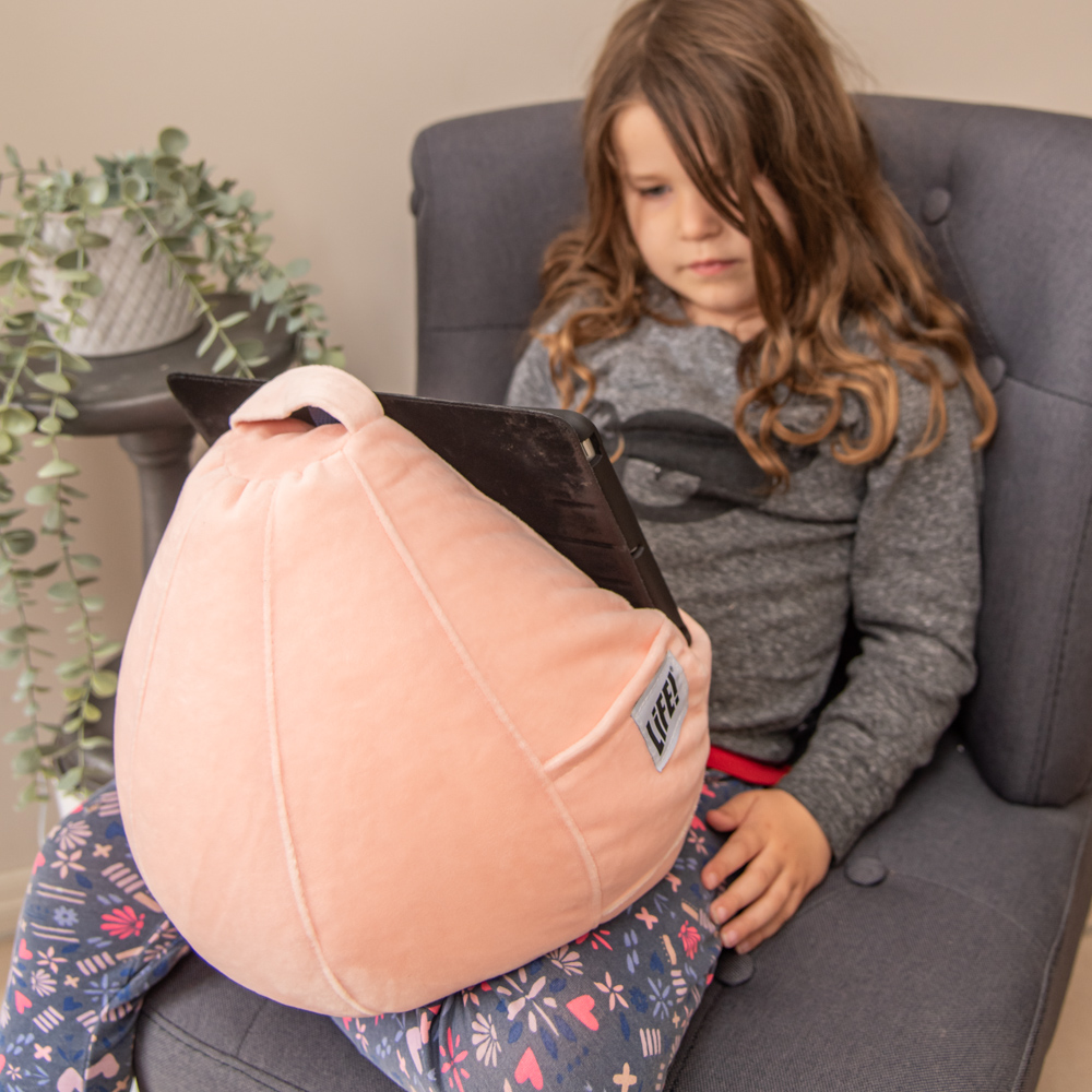 orange pink colored sherbet velvet iCrib bean bag table holder in use with a small girl using an ipad
