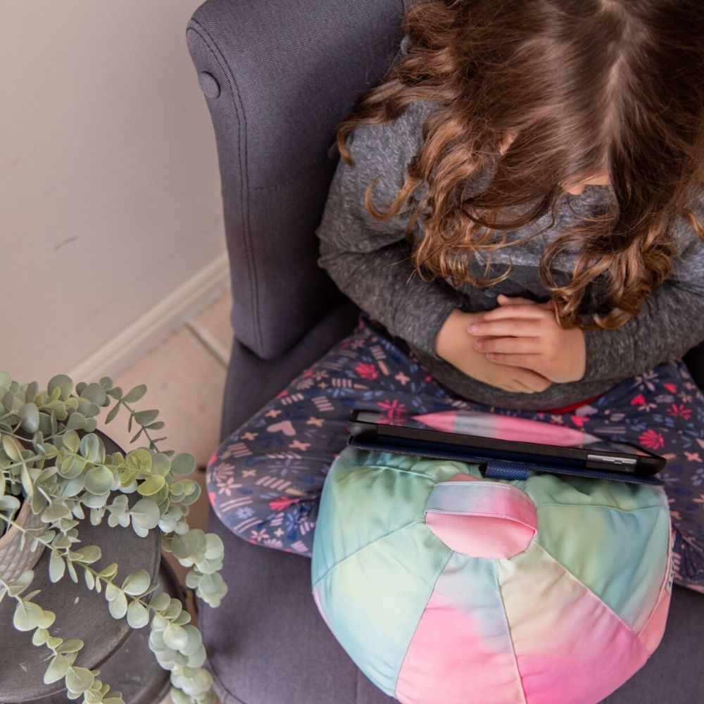 tie dye iCrib from above in use with a child sitting cross legged
