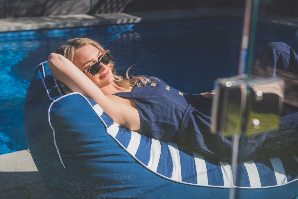woman reclines poolside on a nautical navy and white striped coastal lounger patio proof bean bag