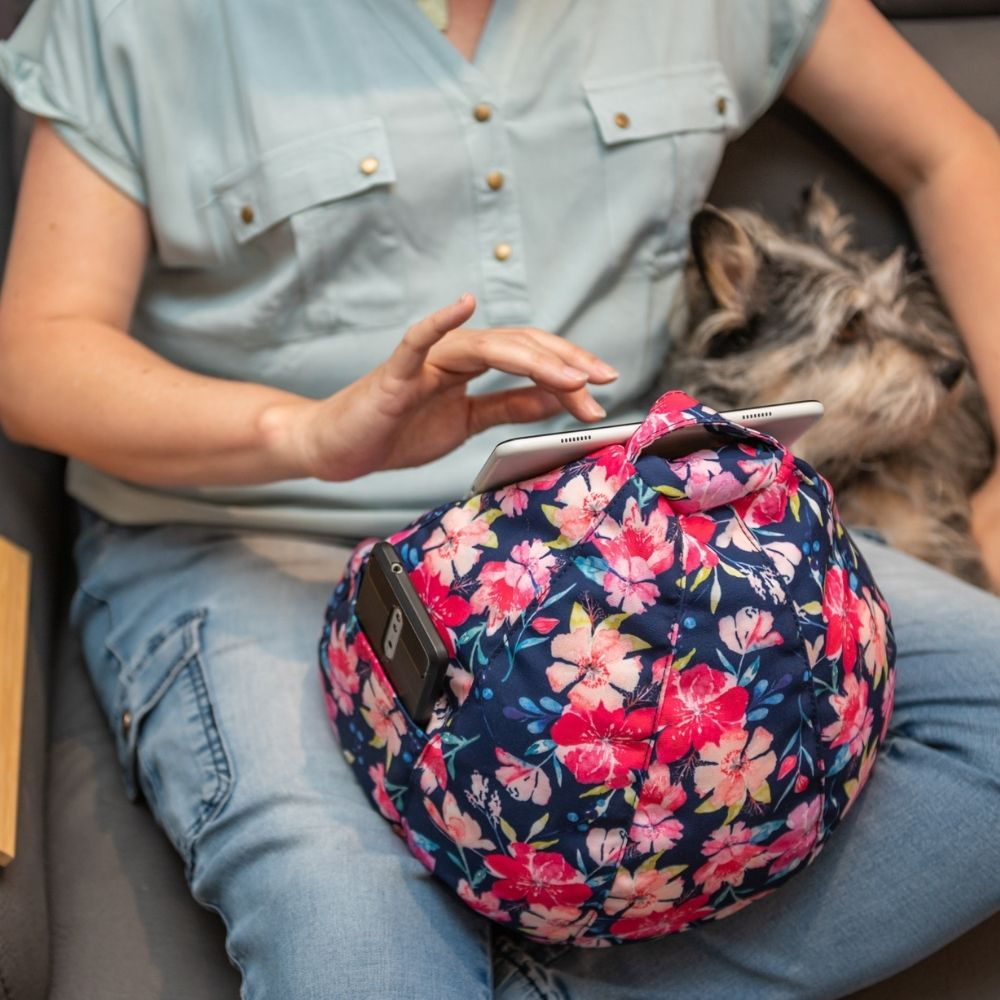 Kalaii floral iCrib in use with an ipad sitting in someone's lap. A phone sits in the storage pocket